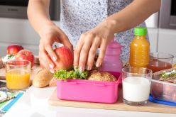 24824647 - young woman making school lunch in the morning